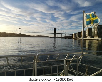 Swedish flag on passenger vessel on the river of Gothenburg towards the Älvsborg Bridge under beautiful shattered clouds under blue sky at dawn