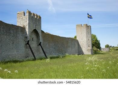 Swedish flag on top of a medieval wall on Gotland island.
