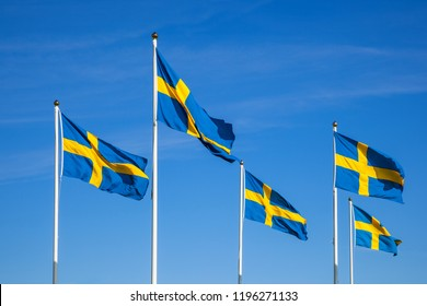 Swedish flags on the national day against a blue sky