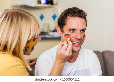 Swedish girl face painting German sports fan before game starts
