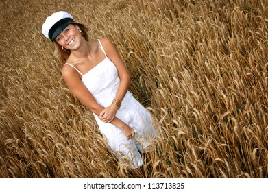 Swedish girl in graduation hat and dress standing in a field of wheat.