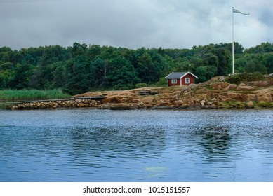 Swedish landscape - lonely small red house with access to water and a jetty, in front of the house the flag of Sweden, bay water in the foreground and trees in the background