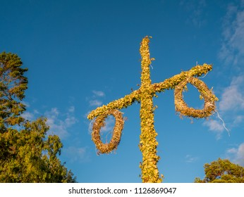Swedish maypole used on midsummer or midsommar in sun set light. Blue sky in background.