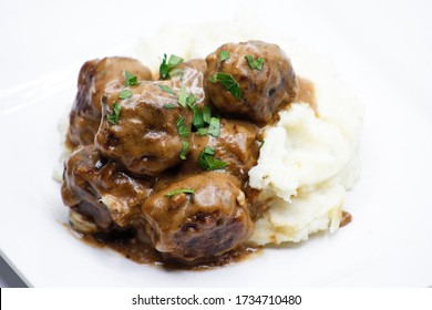 Swedish Meatballs with gravy on mashed potatoes on a white plate with a white background
