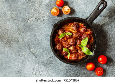 Swedish meatballs with tomato sauce and basil leaf in frying pan top view copy space