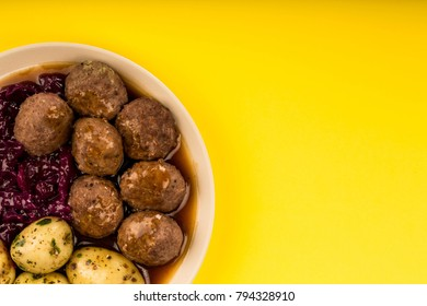 Swedish or Norwegian Meatballs With Boiled Potatoes Red Cabbage And Gravy Meal Against A Yellow Background