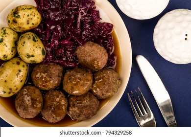 Swedish or Norwegian Meatballs With Boiled Potatoes Red Cabbage And Gravy Meal Against A Purple or Blue Background