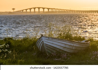 The swedish Oland Bridge with an old weathered rowing boat on land in the front