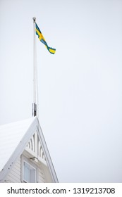 A Swedish pennant flag on top of a roof against an overcast sky.