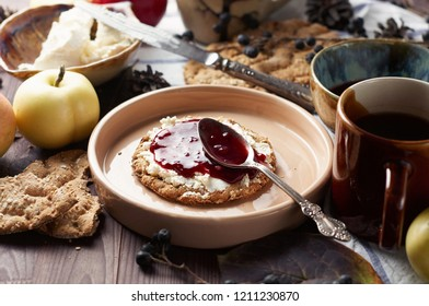 Swedish rye crispbread with cream cheese and raspberry jam. Autumn and winter breakfast concept. Closeup view, selective focus