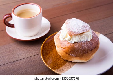 Swedish Semla, traditional Shrove bun, consists of light wheat bread with almond paste and whipped cream filling. cup with coffee.