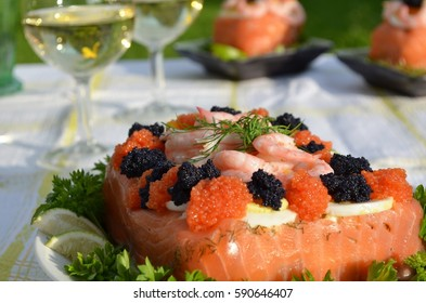 Swedish smörgåstårta, smorgos  cake, with salmon, shrimps, parsely and bread on a summer day.