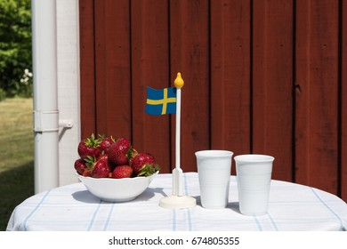 Swedish summer table with fresh strawberries, flag and two mugs by a red plank wall in a garden