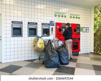 Swedish tall guy take bunch of all kind plastic waste from home to sell to recycling machine at Coop supermarket ,1 April 2018 Sweden Karlstad city