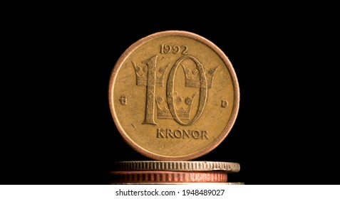 Swedish ten kronor coin, with a pitch black background. 10 SEK, svensk valuta. The Swedish king is visible on the backside, 10 written on the front. The coin is old and well used, cevered by scratches