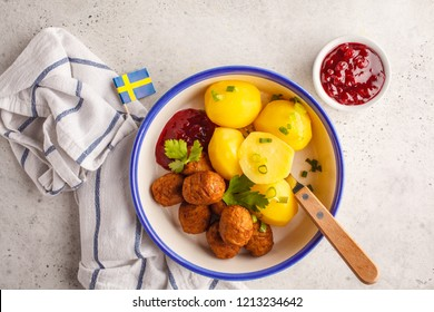 Swedish traditional meatballs with boiled potatoes and cranberry sauce. Swedish food concept.