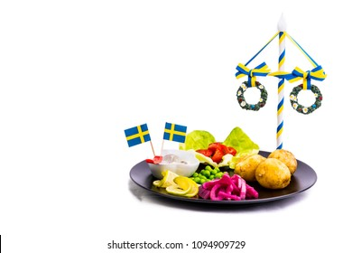 Swedish traditional midsummer food with herring and potatoes and a midsummer rod on a white background