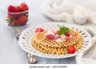 Swedish waffles with strawberries and cream. There is a glass bowl with whole strawberries and a ceramic small bowl of whipped cream in the background. Next to the plate is a fork.