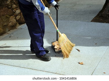 Sweeper, municipal cleaning worker sweeping the autumn leaves on the city sidewalk