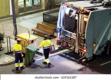 sweeper truck vehicle and cleaner workers at night
