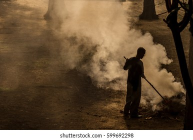 Sweepers garbage waste to burn,Burning pile of garbage, cause of air pollution