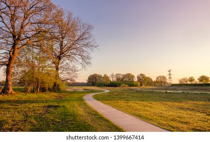 Sweeping bicycle trail in a Dutch farm landscape during sunset. It is located near the small neighbourhood called Tusveld, near the town of Almelo in the Eastern Netherlands.