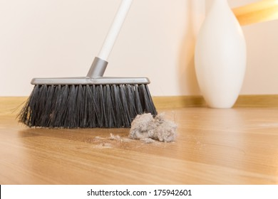 Sweeping dust with black broom on a wooden floor