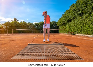 sweeping orange clay on an outdoor tennis court. young woman