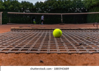 sweeping orange clay on an outdoor tennis court.