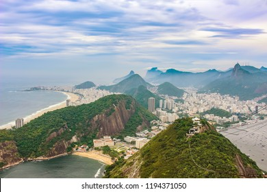 Sweeping View of buildings in the  city of  Rio de Janeiro   with misty hills and statue on mountain, and Copacabana Beach, Brazil , South America