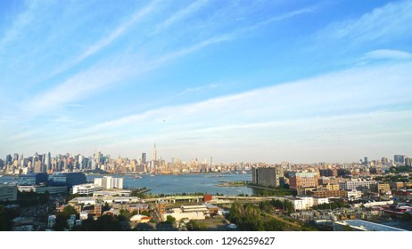 A sweeping view of midtown Manhattan with some of New York City's world-famous and iconic skyscrapers as seen from New Jersey City across the Hudson River in horizontal image format.