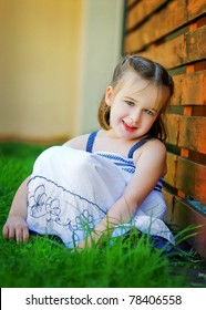 A sweet 4 year old is looking happily at the camera.  She is leaning against a red timber wall.  She looks relaxed and happy.