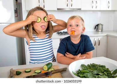sweet 7 years old little girl playing with her 3 years old happy brother at home kitchen having fun with cucumber rod as eyes in siblings learning healthy vegetable nutrition lifestyle concept