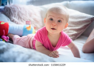 Sweet adorable baby girl lying on a couch looking towards camera. 6-7 months old infant on belly lifting upper body