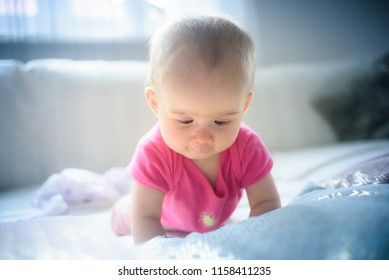 Sweet adorable baby girl lying on a couch looking down. 6-7 months old infant on belly lifting upper body.