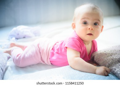 Sweet adorable baby girl lying on a couch looking towards camera. 6-7 months old infant on belly lifting upper body.
