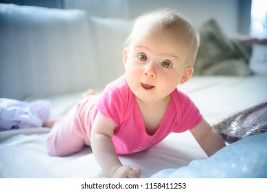 Sweet adorable baby girl lying on a couch looking towards camera. 6-7 months old infant on belly lifting upper body .