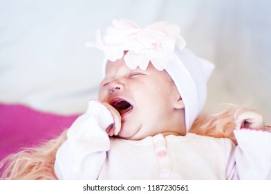 Sweet and adorable Caucasian newborn baby crying. Baby tears, hungry infant concept image. Crying newborn baby. Stomach cramps, baby colic treatment, infant griping pain, uncomfortable infant stock.