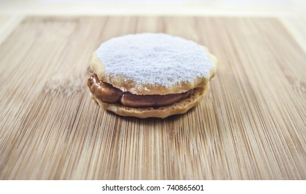Sweet alfajor cookie with white sugar over wood table