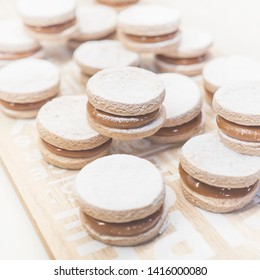 Sweet Alfajores cookie served on the wooden plate. Traditional Argentinian homemade sweets.
