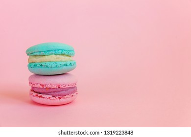 Sweet almond colorful unicorn blue pink macaron or macaroon dessert cake isolated on trendy pink pastel background. French sweet cookie. Minimal food bakery concept. Copy space