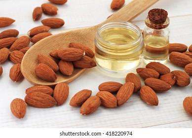 Sweet almond oil in bottles, almond kernels scattered.