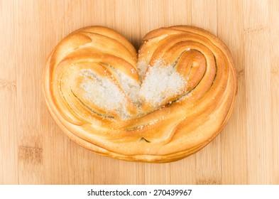 Sweet appetizing bun with sugar in form heart on bamboo board