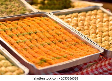 Sweet arab dessert kunefe, kunafa, kadayif with pistachio powder and cheese on the tray in the market.Selective focus.