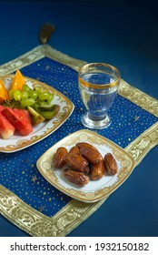 Sweet Arabian dates and fresh fruit slices with glass of water. Iftar is the time to replenish energy levels from healthy and nutritious foods.
