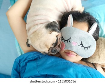 Sweet asian woman with mask and cute puppy pug dog is sleeping rest in the bed.