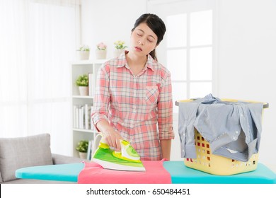 sweet attractive mother doing housekeeping very tired when she ironing clothing standing in living room sleeping resting at home.