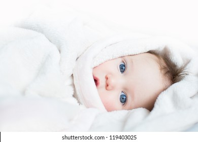 Sweet baby with blue eyes playing peek-a-boo