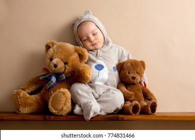 Sweet baby boy in bear overall, sleeping on a shelf with teddy bears stuffed toys.  Shot in  studio on creamy background, shot from above