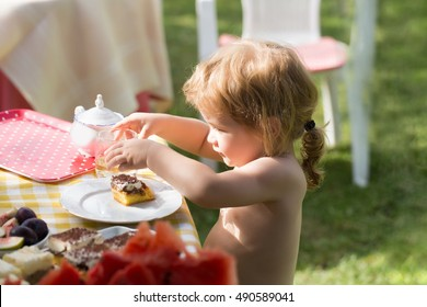 Sweet baby boy blond kid eats delicious dessert cake and drinks juice on sunny summer day on natural background